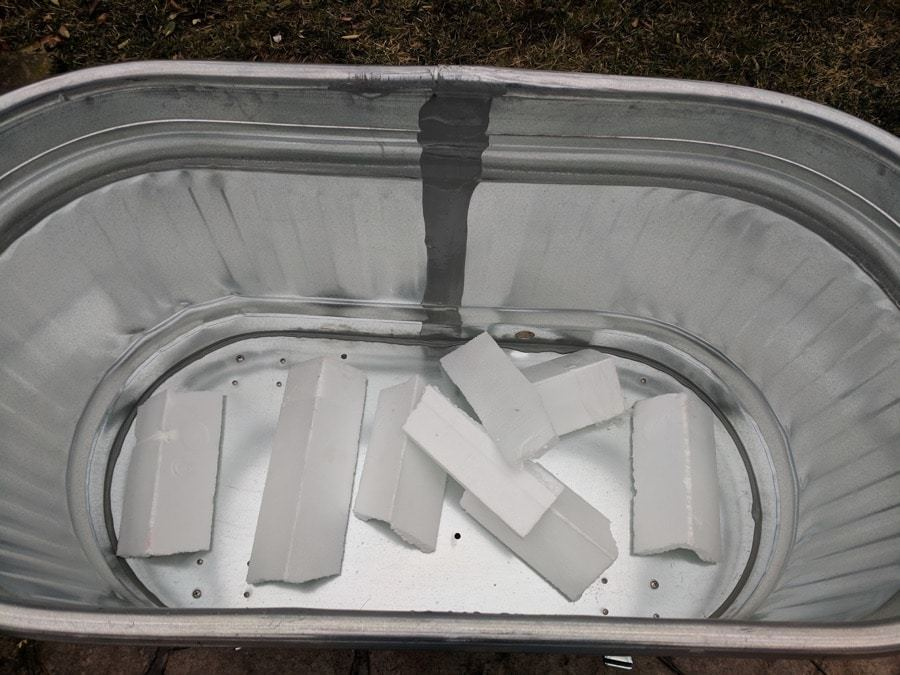 styrofoam lining the bottom of water trough planters